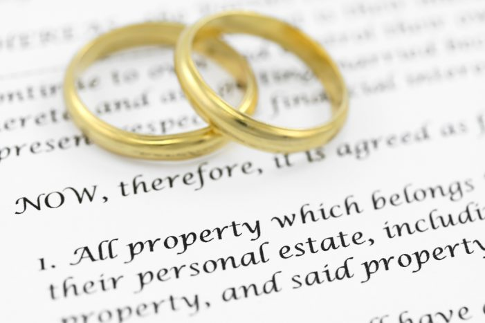 Printed prenuptial agreement with two golden wedding bands