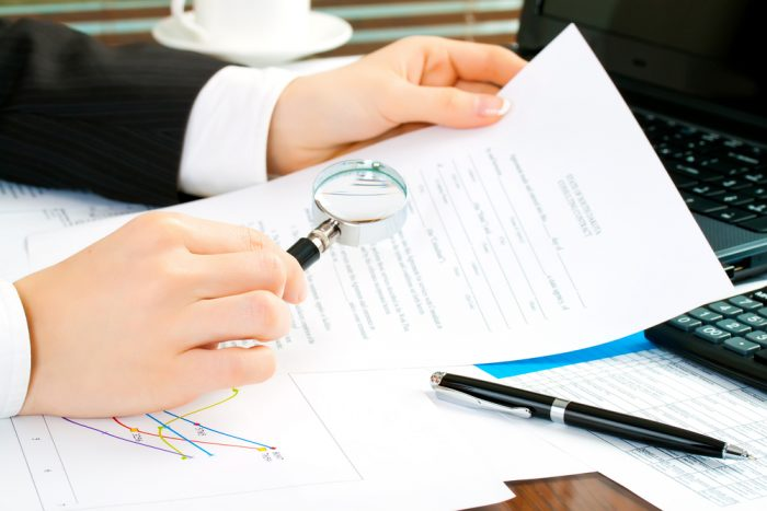 Woman looking at document with magnifying glass