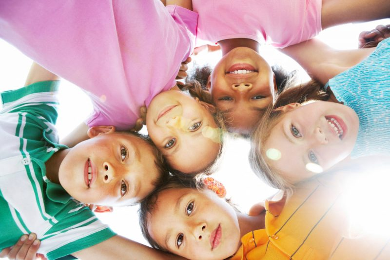 Happy children in a circle looking down