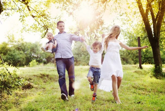 Young family spending time together outside in green nature.