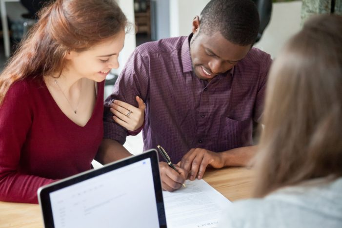 Multiracial couple signing documents at meeting