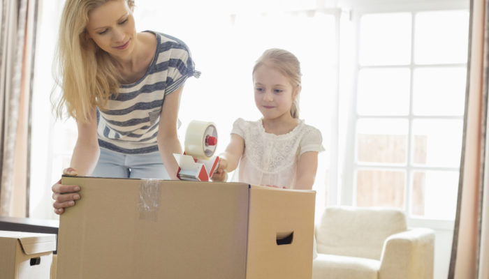 Mother and daughter packing cardboard box at home