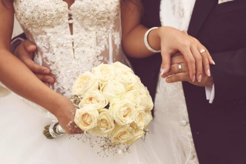 Detail of bride's roses bouquet and hands holding