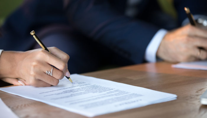 Close up view of woman and man signing document contract