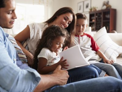 Young family of four sitting on the sofa reading book together in their living room