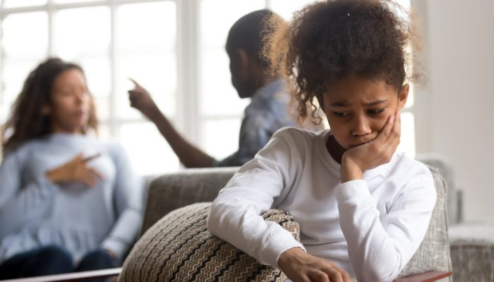Upset girl sitting alone, parents quarreling